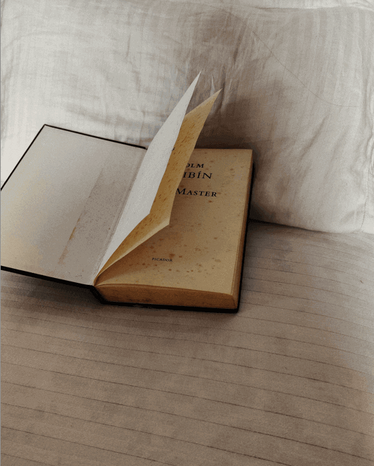 An open book on the bed for monsoon book recommendations.