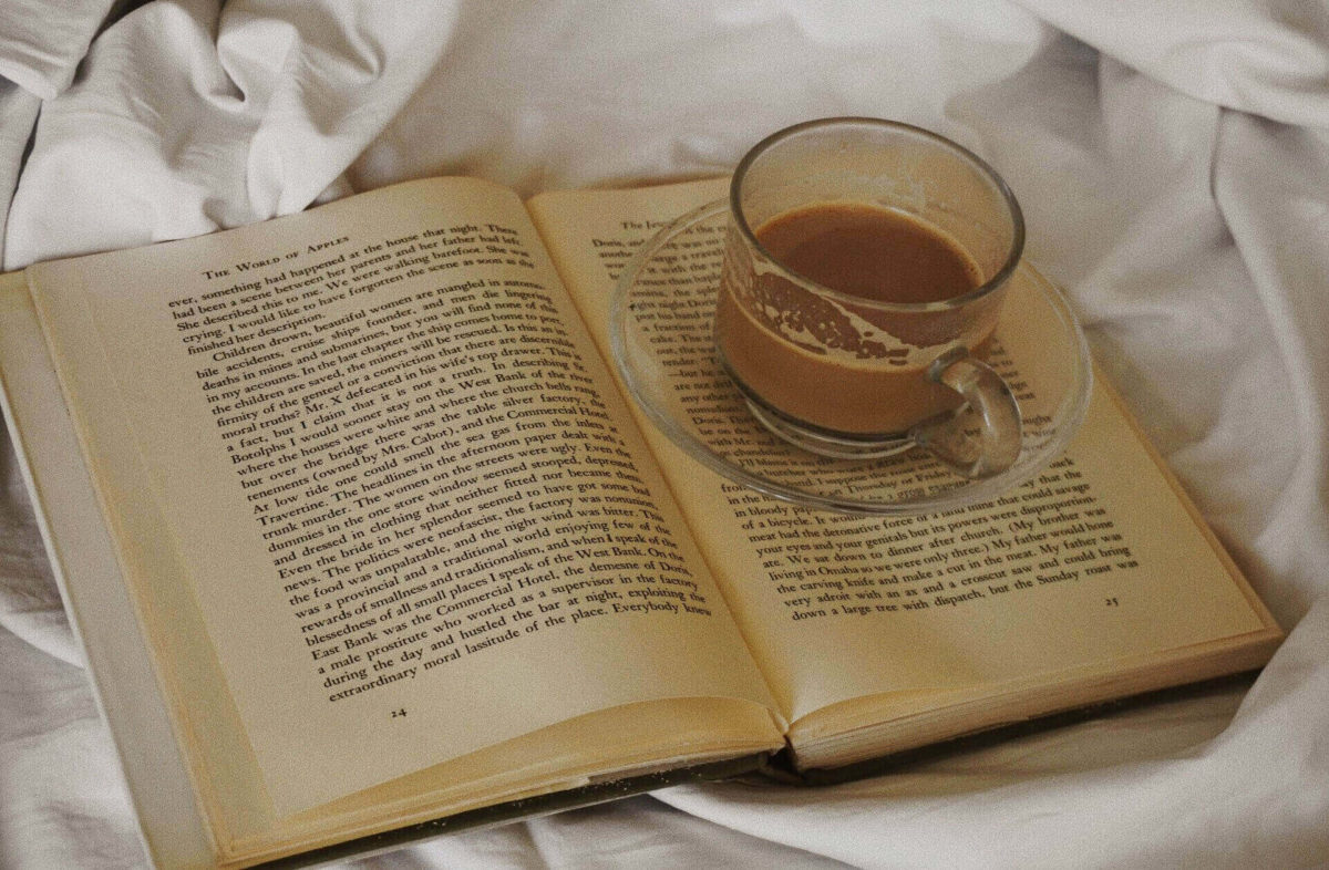 An open book with a coffee cup on top for holiday book recommendations.